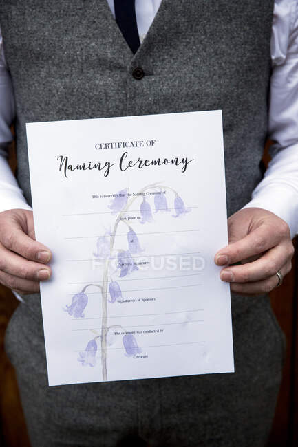 Close up of man holding certificate for a naming ceremony. — Stock Photo