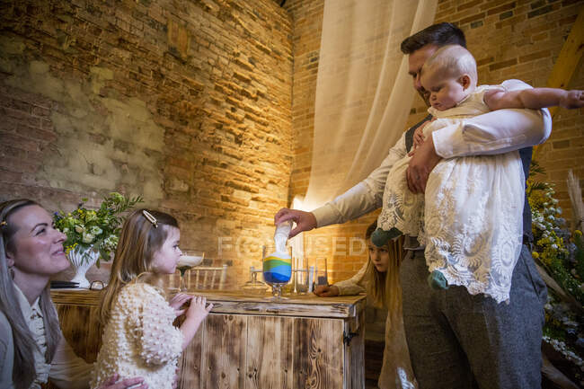 Family pouring coloured sand into glass jar during naming ceremony in an historic barn. — Stock Photo