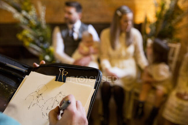 Over the shoulder view of artist sketching family during naming ceremony in an historic barn. — Stock Photo