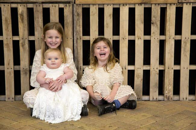 Портрет трьох молодих сестер під час церемонії найменування в історичному сараї, сидячи на підлозі, усміхаючись до камери.. — стокове фото