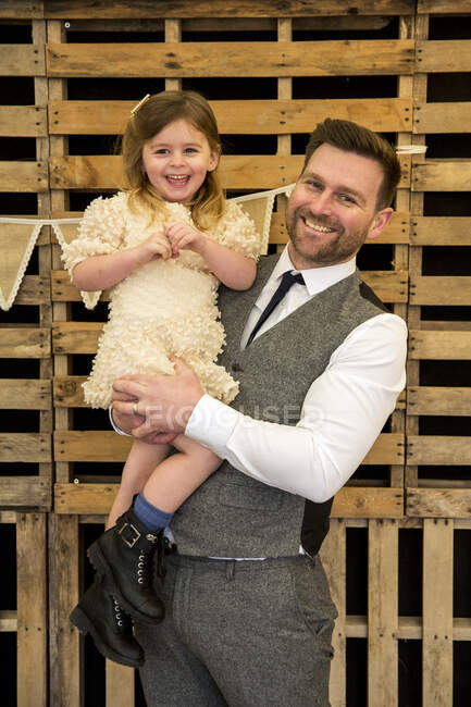 Portrait of bearded man hugging his young daughter during naming ceremony in an historic barn. — Stock Photo