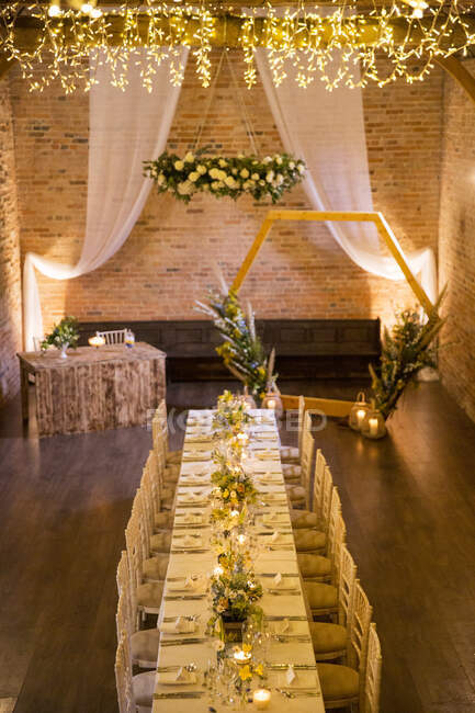 Long dining table with festive place settings for a naming ceremony in an historic barn. — Stock Photo