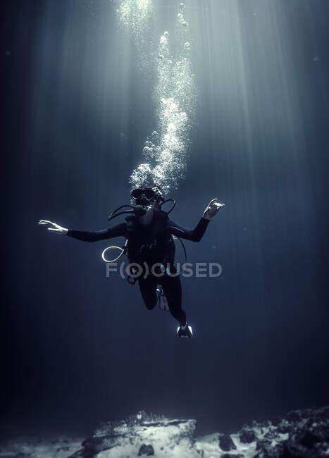 Vista subacquea del subacqueo che indossa muta, occhiali subacquei e bombola di ossigeno, bolle d'aria in aumento. — Foto stock