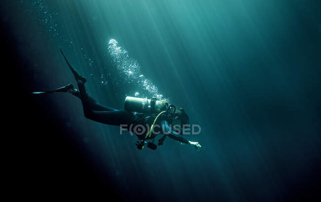 Underwater view of diver wearing wetsuit, diving goggles and oxygen cylinder, air bubbles rising. — Stock Photo