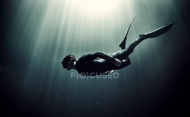 Vista subacquea del subacqueo che indossa muta e pinne, luce solare che filtra dall'alto. — Foto stock