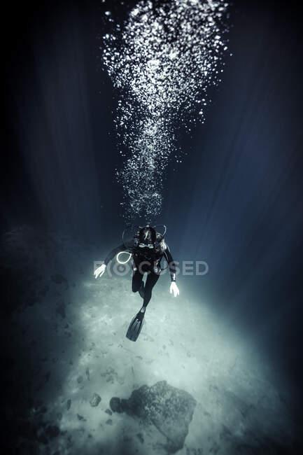 Vista subacquea ad alto angolo del subacqueo che indossa muta e pinne, bolle d'aria in aumento. — Foto stock