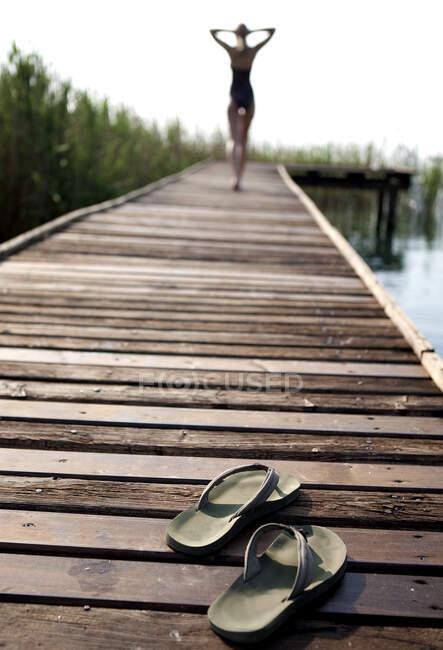 Vista posteriore della donna in costume da bagno che cammina lungo un molo, mani sopra la testa, paio di infradito in primo piano. — Foto stock