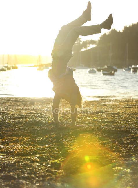 Hombre haciendo un puesto de mano en la orilla, mar y amarre veleros en el fondo, la luz del sol. - foto de stock
