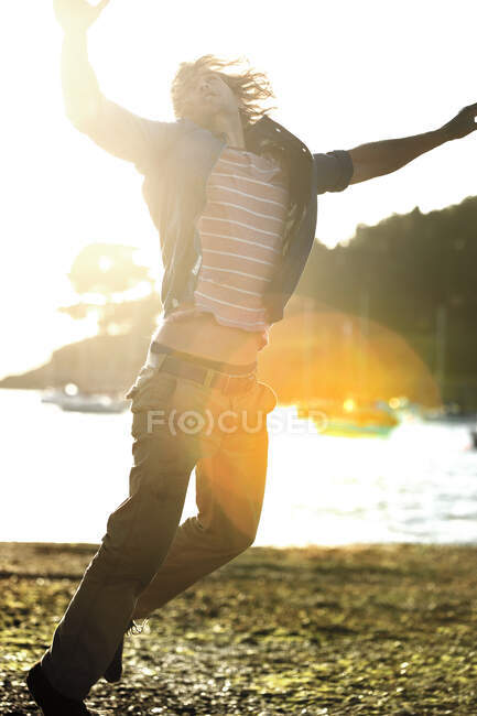 Giovane che salta su una spiaggia di ciottoli, braccia alzate, barche a vela ormeggiate sullo sfondo, luce del sole. — Foto stock
