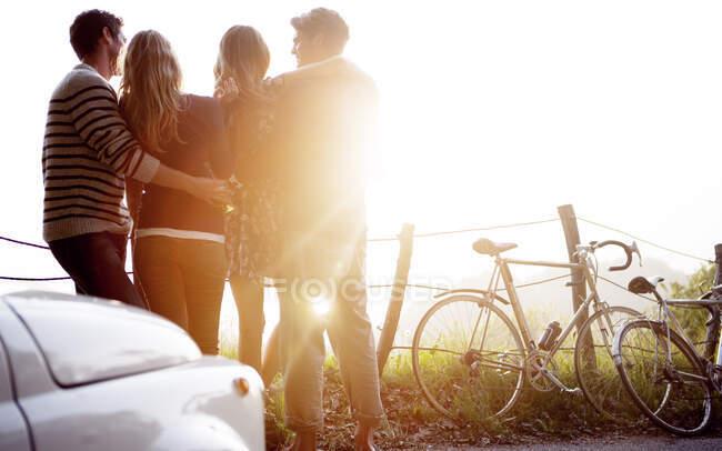 Quattro persone in piedi accanto a una strada, auto parcheggiata e biciclette appoggiate a una recinzione, luce del sole. — Foto stock