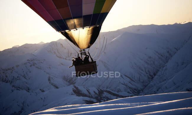 Люди на повітряній кулі посеред повітря над засніженою горою.. — стокове фото