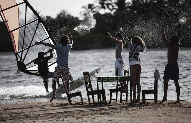 Piccolo gruppo di uomini e donne in piedi su una spiaggia di sabbia intorno a tavolo e sedie, braccia alzate, bottiglie in mano, guardando un windsurfer. — Foto stock