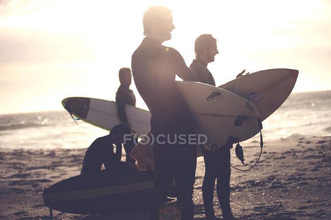 Quattro uomini che indossano mute in piedi su una spiaggia di sabbia, portando tavole da surf. — Foto stock