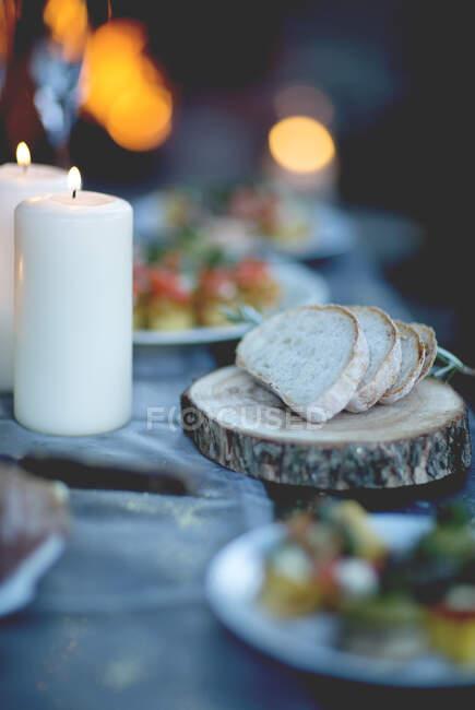 Cierre de dos velas encendidas y rebanadas de pan sobre tabla redonda de madera. - foto de stock