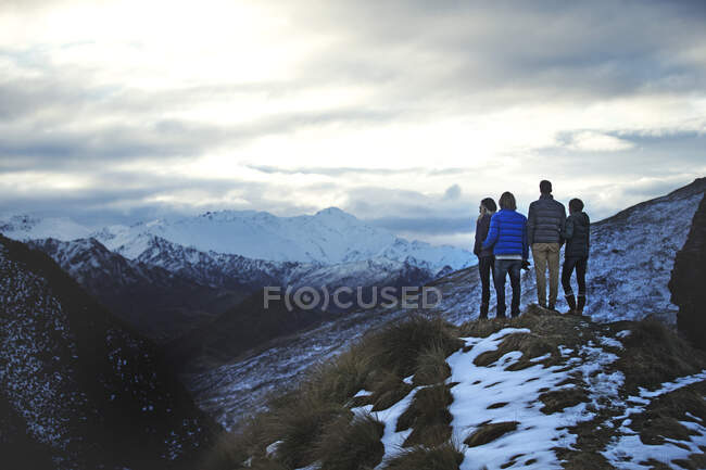 Rear view of four people standing side by side on a mountain, snow-capped peaks in the distance. — Stock Photo