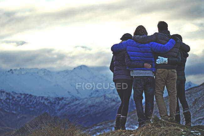 Rear view of four people standing arm in arm on a mountain, snow-capped peaks in the distance. — Stock Photo