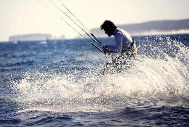 Vista laterale dell'uomo kitesurf sull'oceano. — Foto stock