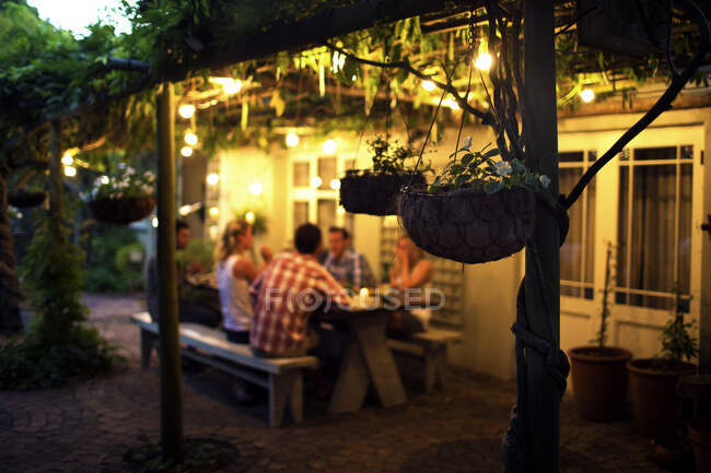 Group of people sitting outdoors at a table, hanging baskets in foreground, evening. — Stock Photo