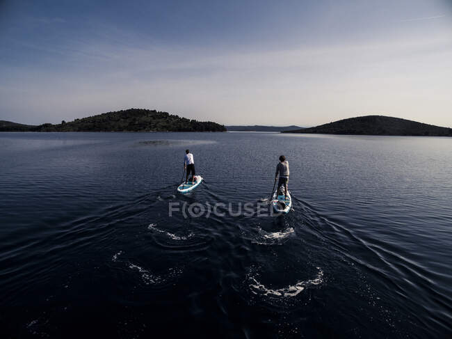 Alto ángulo de tiro de dos personas en paddleboards. - foto de stock