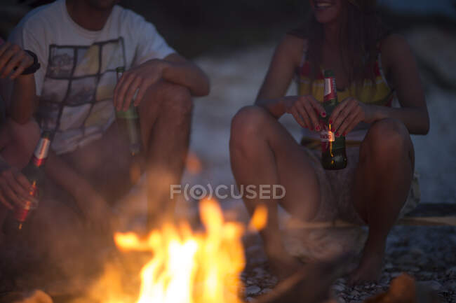 Group of young people gathering on a beach around a campfire. — Stock Photo