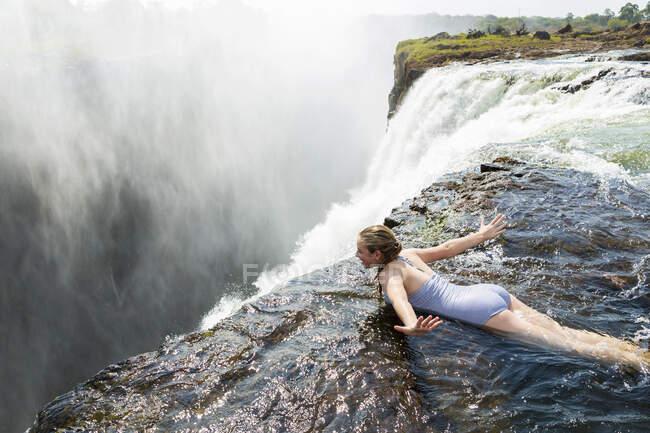 Jeune fille dans l'eau à la piscine Devils couchée sur son devant, les bras écartés, au bord de la falaise des chutes Victoria. — Photo de stock