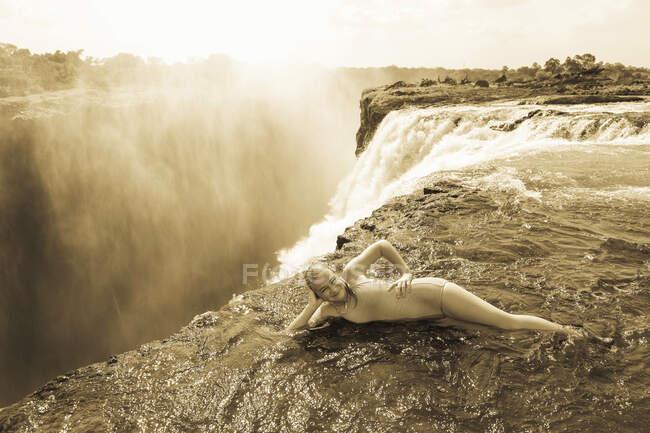 Jeune fille dans l'eau à la piscine Devils appuyé sur son coude, au bord de la falaise des chutes Victoria. — Photo de stock