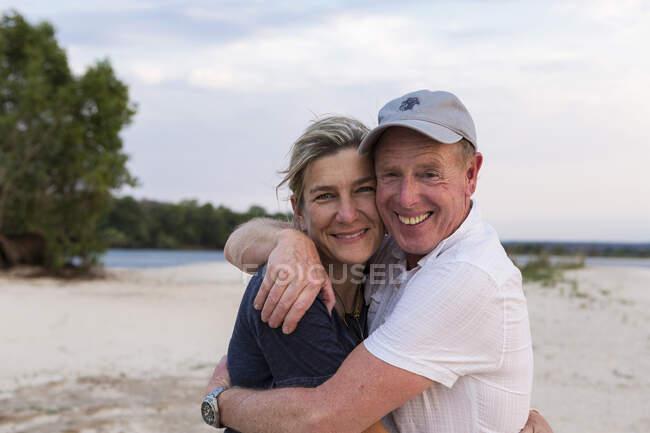Pareja madura abrazándose a las orillas del río Zambeze. - foto de stock