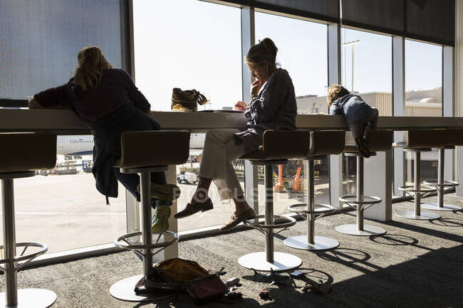 Reife Frau und zwei Kinder sitzen auf hohen Hockern in einer Abflughalle mit Blick über das Vorfeld des Flughafens. — Stockfoto