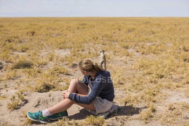 Fille de 12 ans assise à regarder des suricates émerger de leurs terriers, dans le désert du Kalahari. — Photo de stock