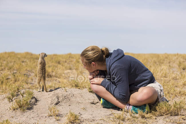 Fille de 12 ans assise à regarder Meerkat émerger du terrier, dans le désert du Kalahari. — Photo de stock