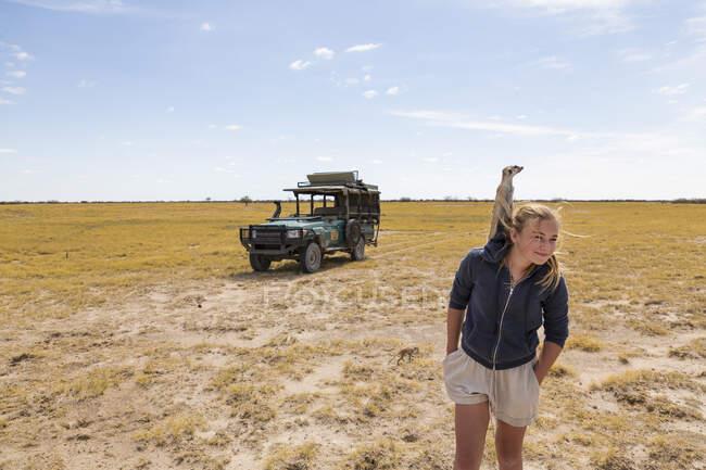 Fille de 12 ans avec Meerkat sur la tête, désert du Kalahari — Photo de stock