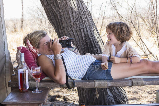 Mother taking pictures of her five year old son, relaxing in the shade of a tent in a safari camp. — Stock Photo