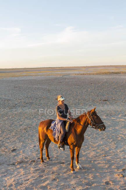 Uma mulher a cavalo ao pôr do sol em espaço aberto. — Fotografia de Stock