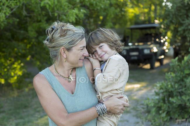 Donna, madre che porta suo figlio di cinque anni in un campo di riserva naturale. — Foto stock