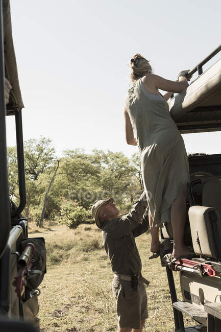 Woman climbing on safari vehicle. — Stock Photo