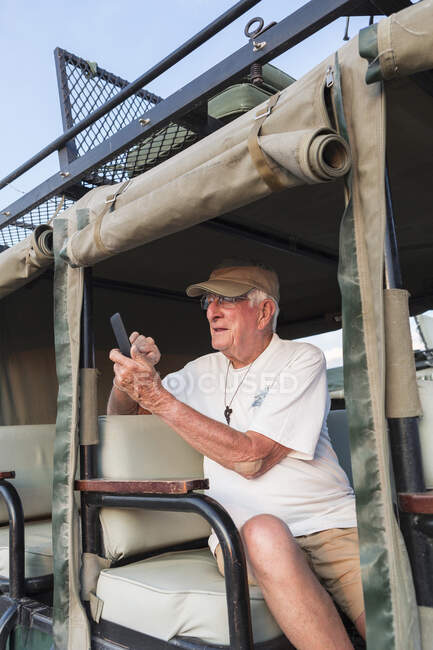 Homem sênior tirando foto com telefone inteligente, deserto de Kalahari, Makgadikgadi Salt Pans, Botswana — Fotografia de Stock