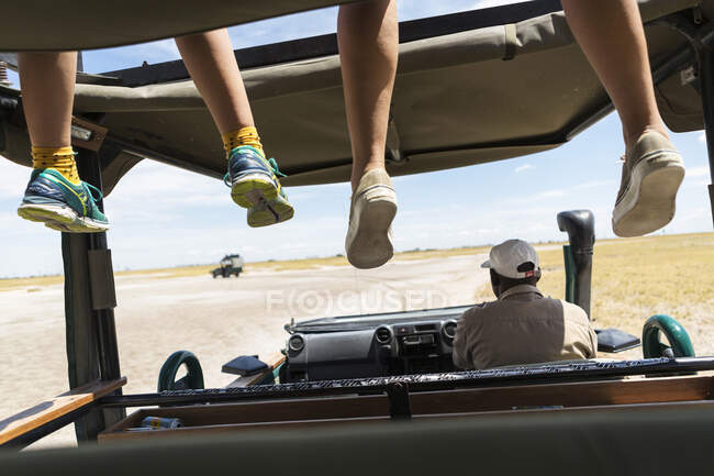A safari vehicle, one person in the driving seat and two sitting of dangling legs of passengers on the observation platform. — Stock Photo