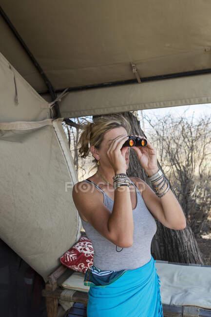 Femme mûre par une tente dans un camp de réserve faunique à l'aide de jumelles. — Photo de stock