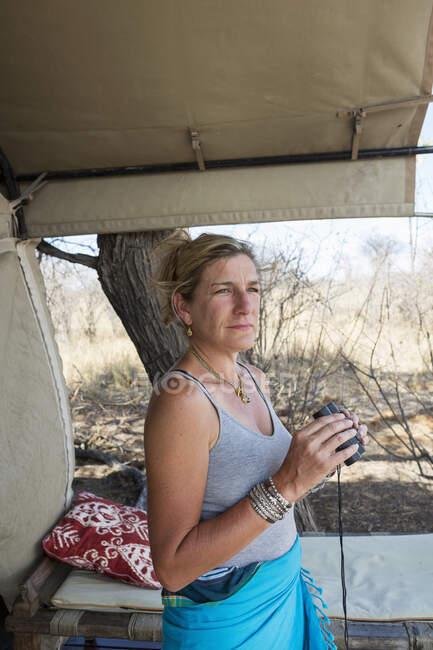 Femme mûre près d'une tente dans un camp de réserve animalière tenant des jumelles — Photo de stock