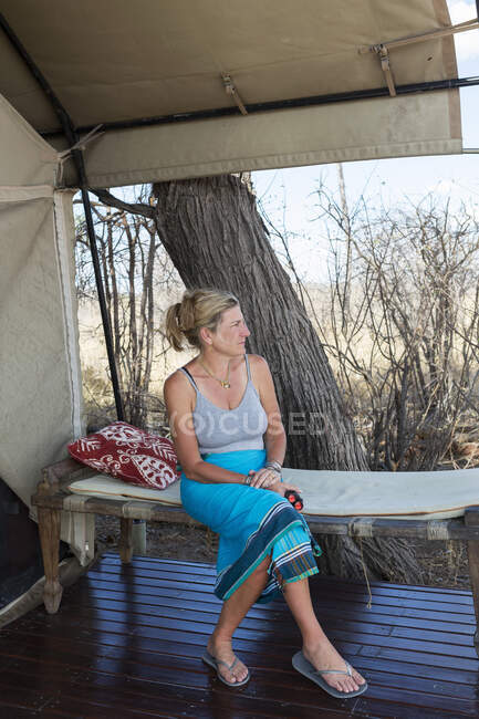 Femme mûre assise sous une toile, près d'une tente dans un camp de réserve faunique. — Photo de stock