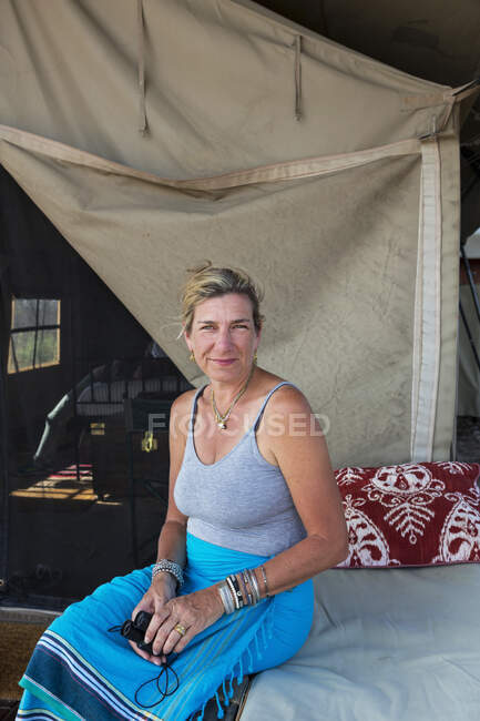 Une femme assise sur un lit dans une tente dans un camp de réserve faunique. — Photo de stock