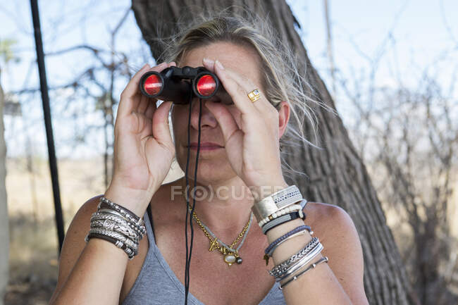 Une femme utilisant des jumelles dans un camp de réserve faunique. — Photo de stock