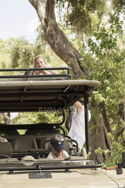 Tre persone, una donna seduta nel veicolo e due bambini che salgono sulla piattaforma di osservazione sotto gli alberi. — Foto stock