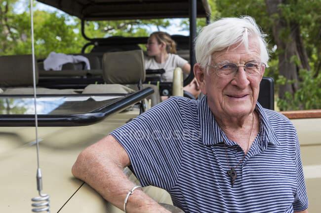 Älterer Mann steht an einem Safari-Fahrzeug und lächelt in die Kamera — Stockfoto