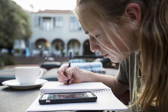 Une adolescente qui utilise un stylo et du papier pour prendre des notes, regarder un téléphone intelligent, écrire un journal ou faire ses devoirs. — Photo de stock