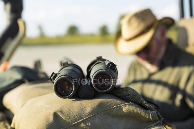 Binoculars on the dash of a safari vehicle, a safari guide in the background. — Stock Photo