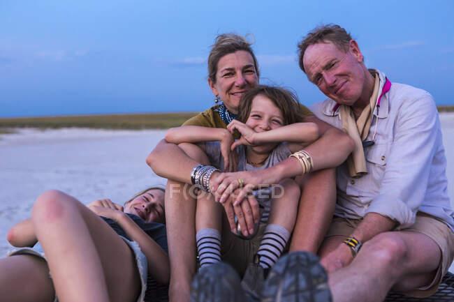 Smiling family on top of safari vehicle, Nxai Pan, Botswana — Stock Photo