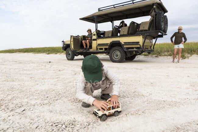 6 anno vecchio ragazzo giocare con giocattoli, Nxai Pan, Botswana — Foto stock