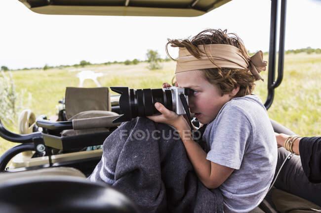 Niño de 6 años tomando fotos de vehículo safari, Botswana - foto de stock