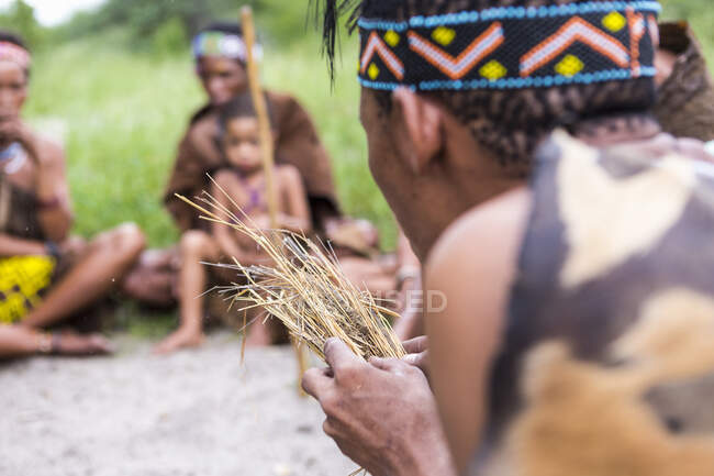 San People, a bushman creating fire from dry kindling, a cultural demonstration. — Stock Photo